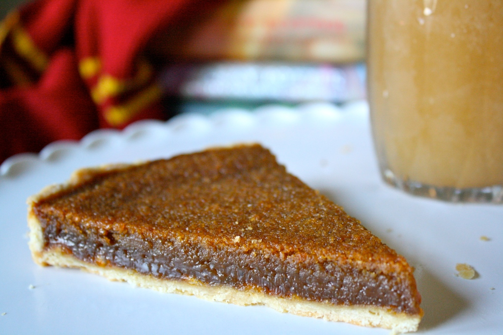 Slice of treacle tart on plate with butterbeer and Harry Potter