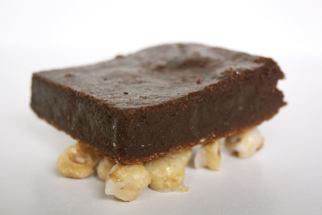 Nutella brownies sitting on hazelnuts by Edible Times