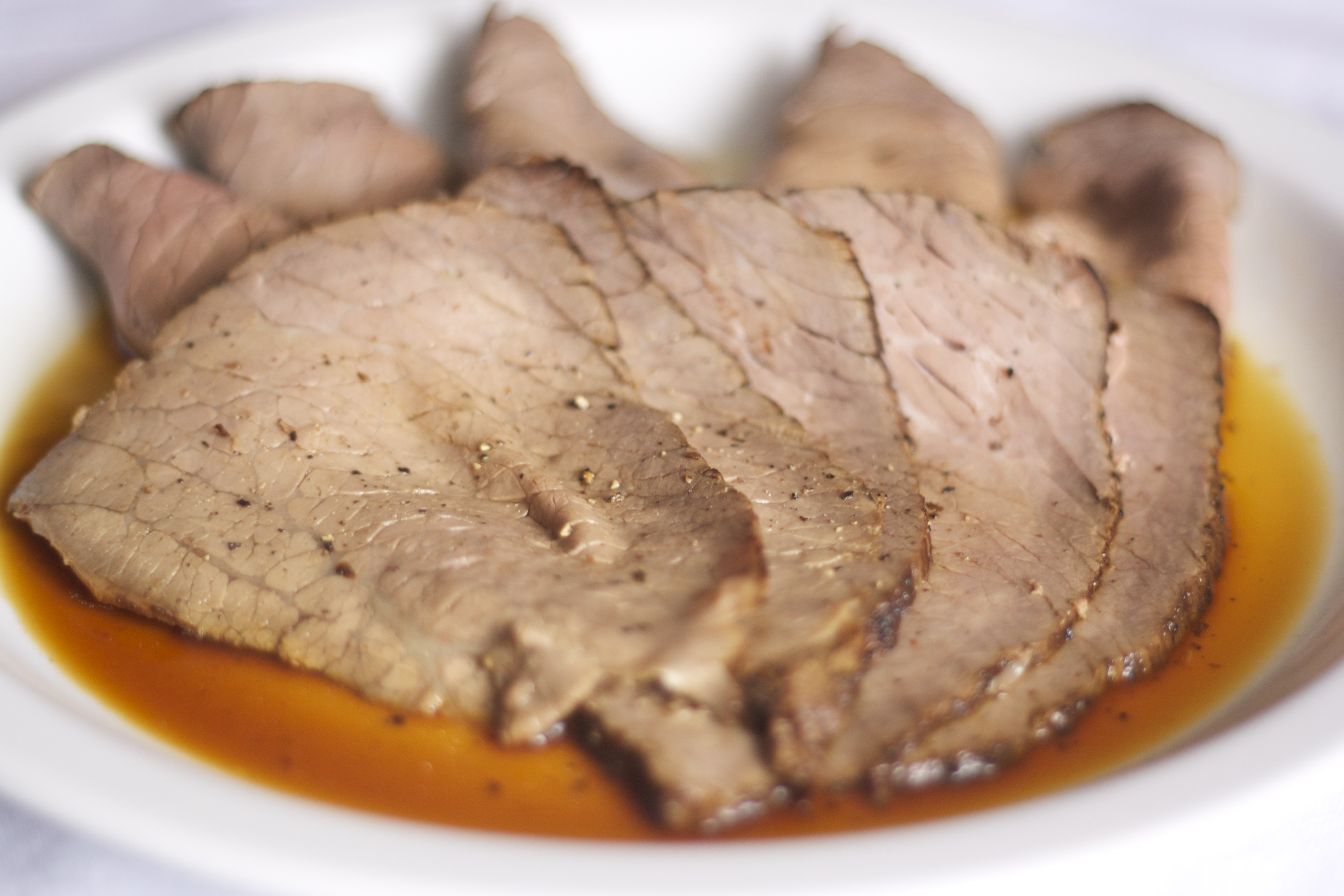 GAPS diet legal roast beef recipe sliced, on plate with pan drippings.