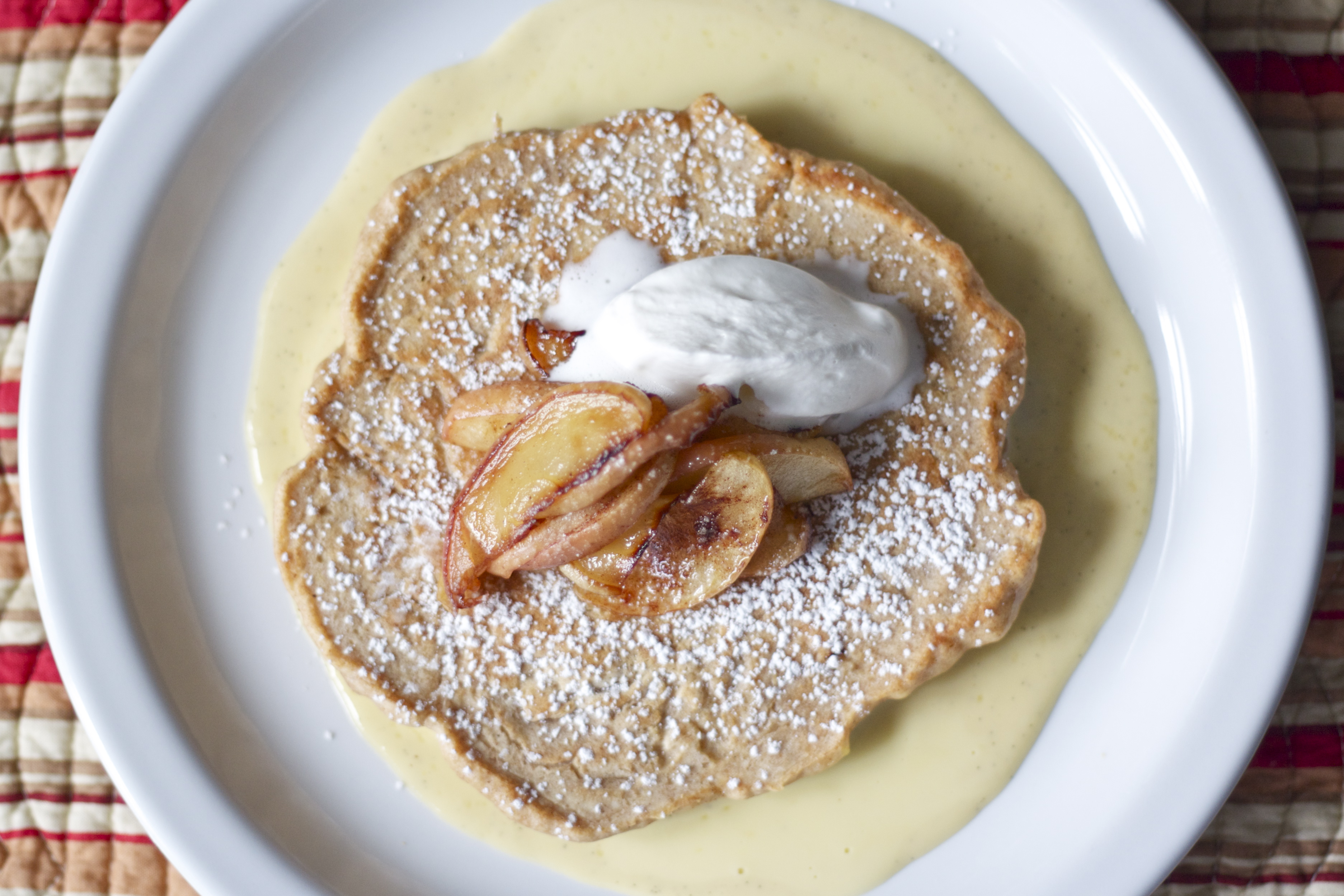 Caramelized apple pancakes on creme anglaise with whipped cream.