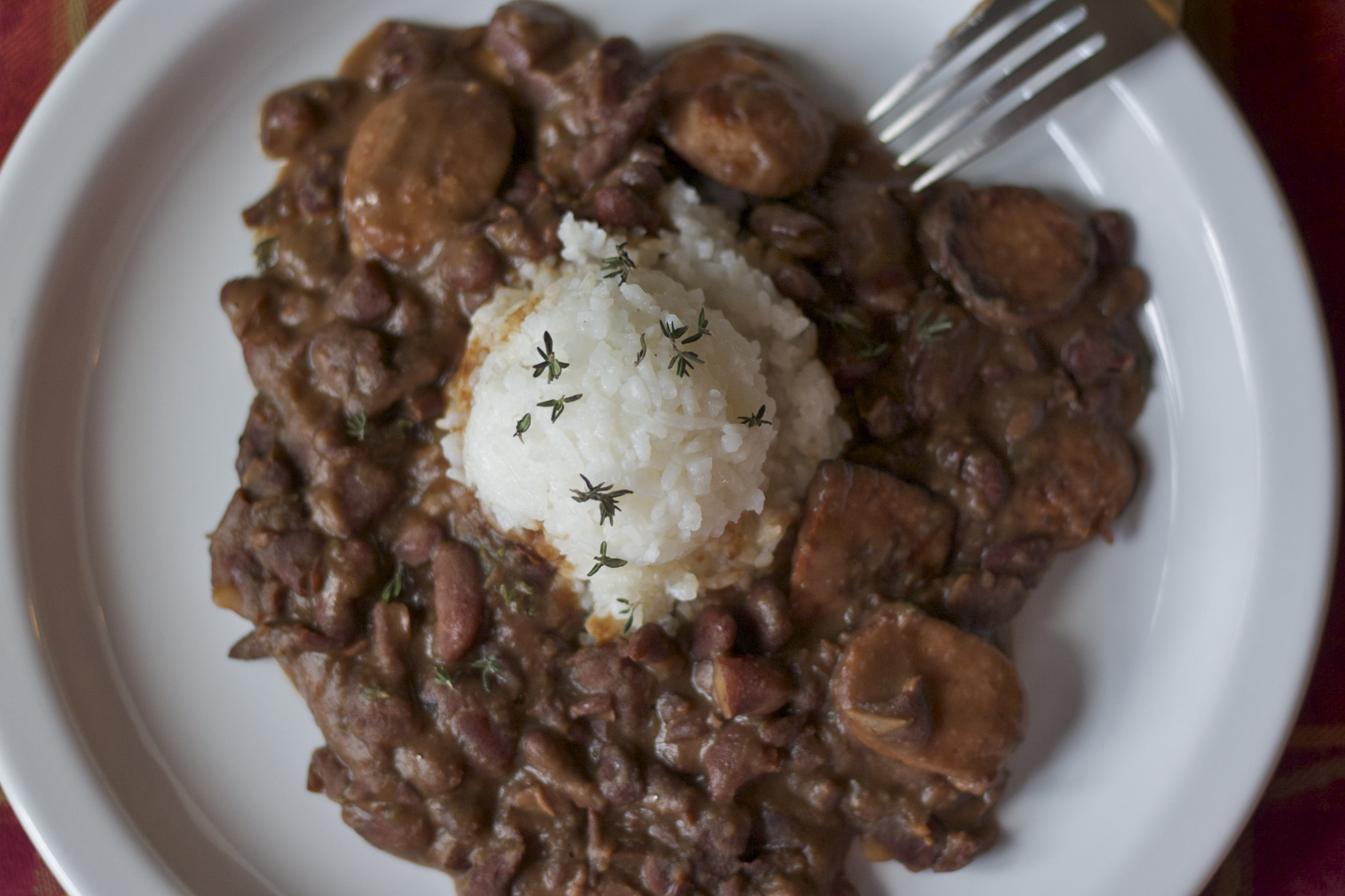 Traditional New Orleans red beans and rice on white plate.